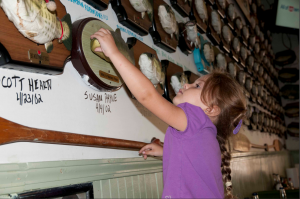 Hali Hirrill adds to the collection of Big Mouth Billy Bass at the Flying Fish restaurant in Little Rock, Arkansas